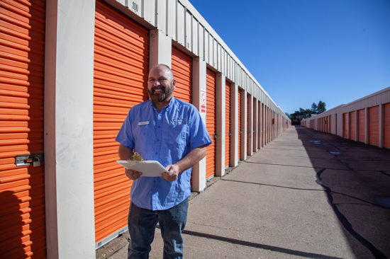 Service representative in front of the orange storage containers