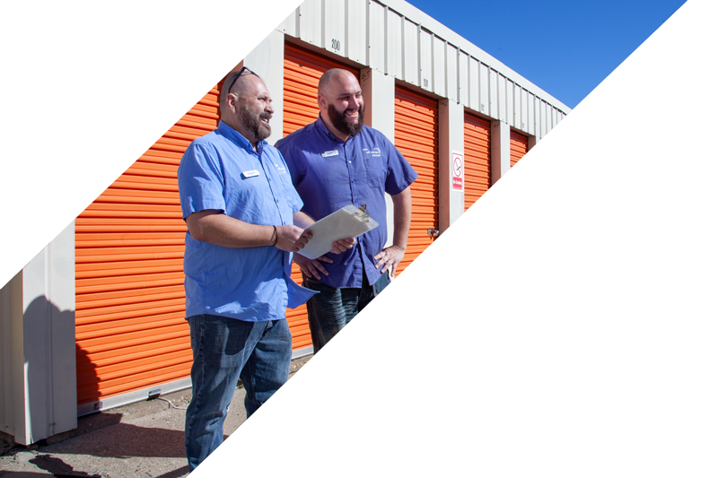 Two service representatives with a clipboard in front of the orange storage containers